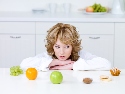 Woman choosing between fruits and cakes