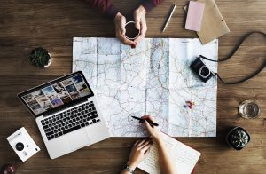 two people sharing an adventure with a map, laptop, coffee and useful clutter, declutter your space